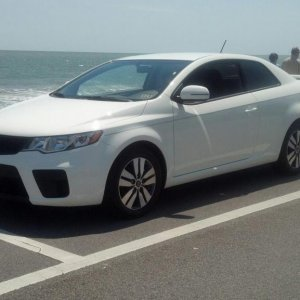 White Kia Forte Koup at the beach.